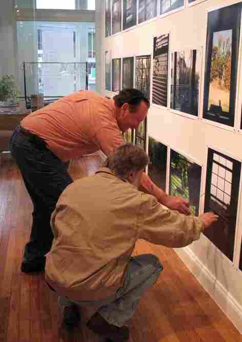 """Lease's photo project, entitled """"Send Me the Pillow You Dream On,"""" involved 43 participants each sending him four separate photos.  Here, guests examine one part of the exhibit: photos of 43 distinct window views."""
