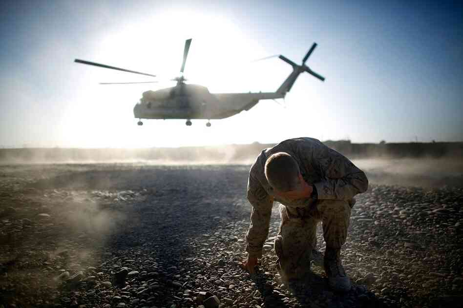"The Marines of the 2nd Battalion, 8th Regiment — known as ""America's Battalion"" — have been fighting the Taliban in southern Afghanistan's Helmand province since July. Here, Lt. Col. Christian Cabaniss, the battalion commander, covers his eyes and hits the ground as a Marine helicopter lifts off from Forward Operating Base Delhi."