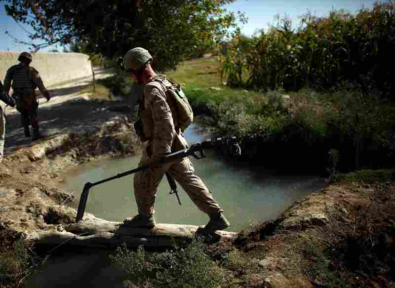 A Marine carries a metal detector near Garmsir in Helmand province in a sweep for roadside bombs. That day, Marines found and destroyed three homemade explosive devices during their six-hour patrol.