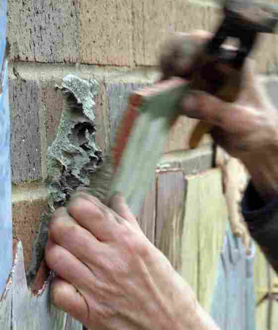 Judith uses a special wrench to fine-tune the cuts and then uses mortar to affix the tile to the wall.