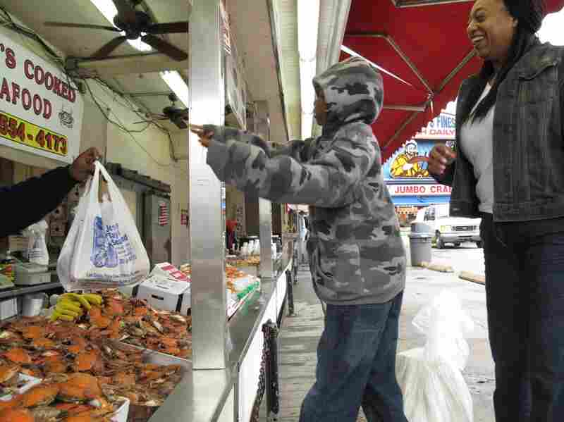 Charles Tucker and his mother Endia Thomas load up on cooked crabs for the weekend.