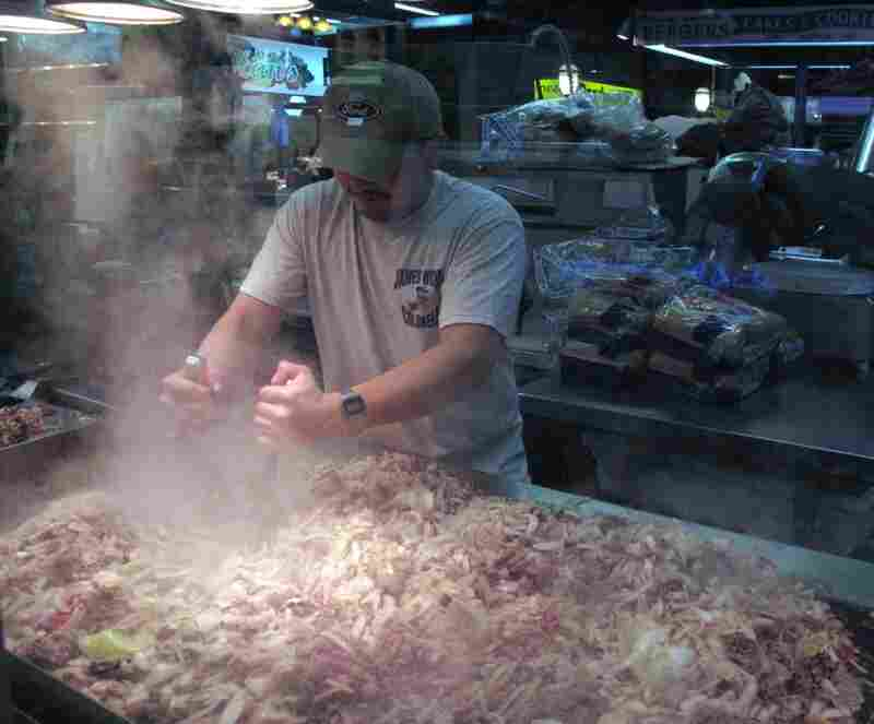 Lunch is the busiest time of day at the market.  Here, a cook grills meat and onions for cheesesteaks.