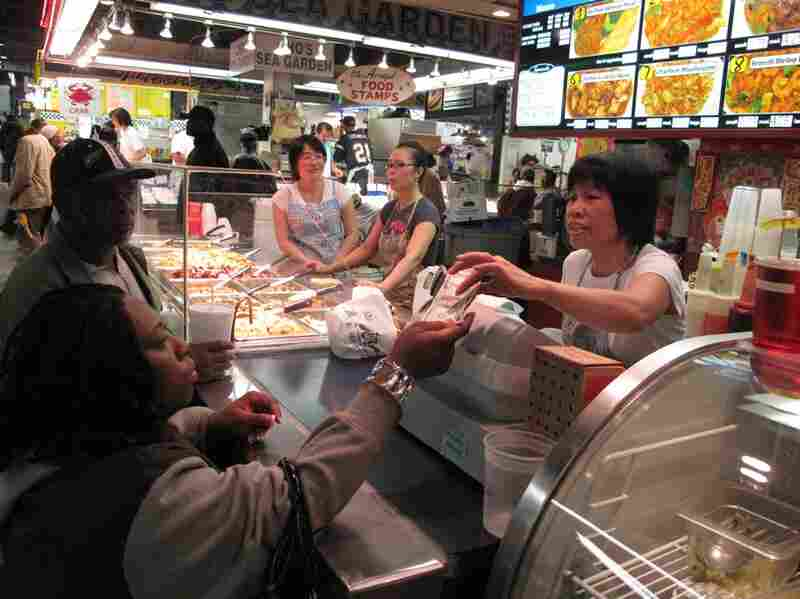 A customer pays for her order of Chinese food before the lunch rush begins.