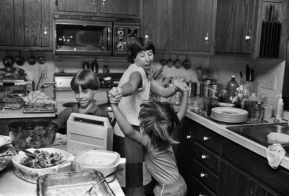 Judy and Sara stage an impromptu dance in the kitchen. Judy is just as likely to dance and sing through the grocery store. May 1986.