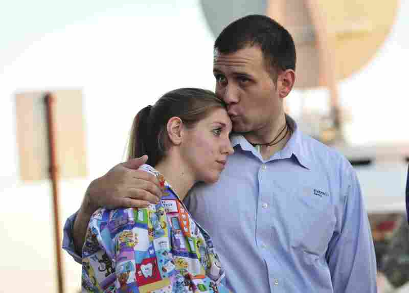 Daniel Clark kisses his wife, Rachel Clark, while they wait for Fort Hood to reopen after Thursday's shooting so they can pick up their 5-year-old child at a day care center.