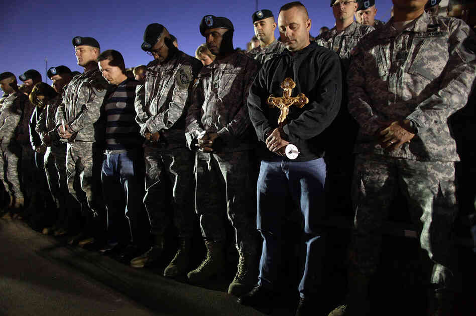 Soldiers bow their heads in prayer during a vigil at Fort Hood on Friday.