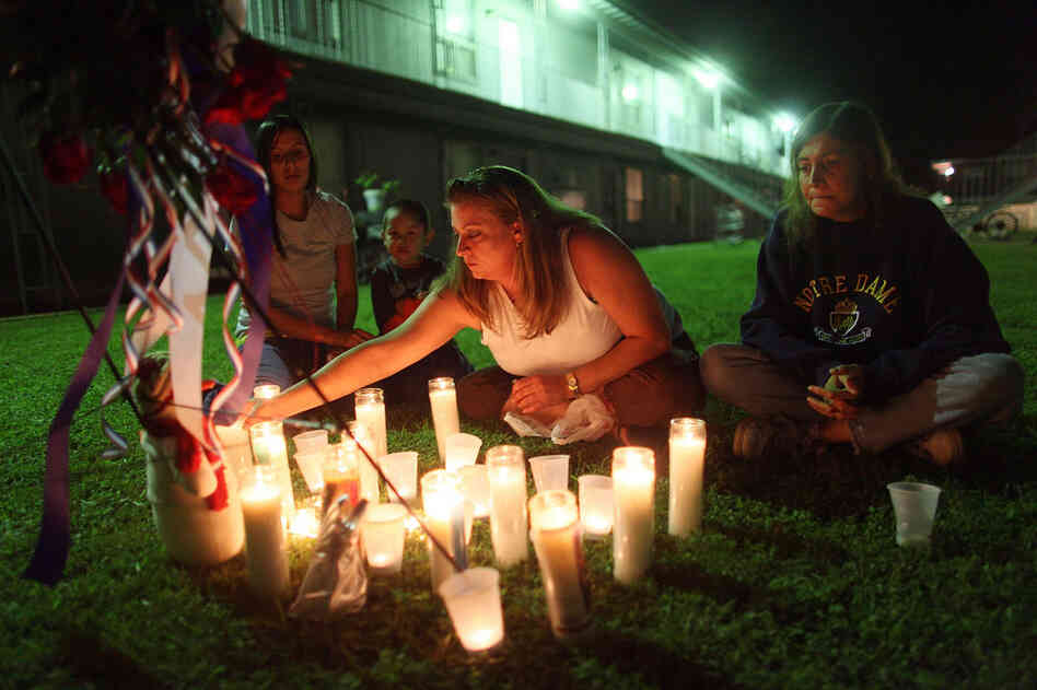 Kolleen Alldridge (from left), Gavyn Alldridge, Kim Rosenthal and Alice Thompson light candles Saturday at a small memorial in the courtyard of the apartment complex where Maj. Nidal Malik Hasan lived prior to the Fort Hood shooting.