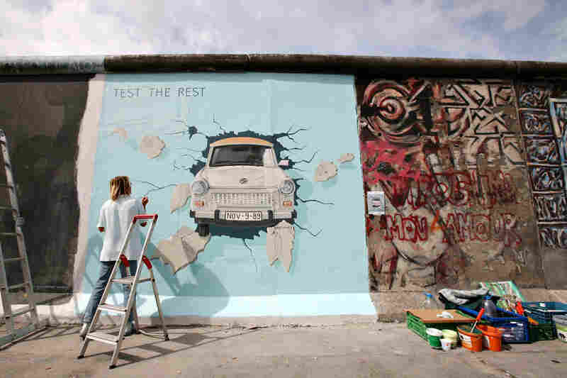 Birgit Kinder works on her painting Trabi on a portion of the Berlin Wall known as the East Side Gallery, on July 8, 2009.  Ninety-one international artists gathered to repaint their original creations on the concrete slabs.