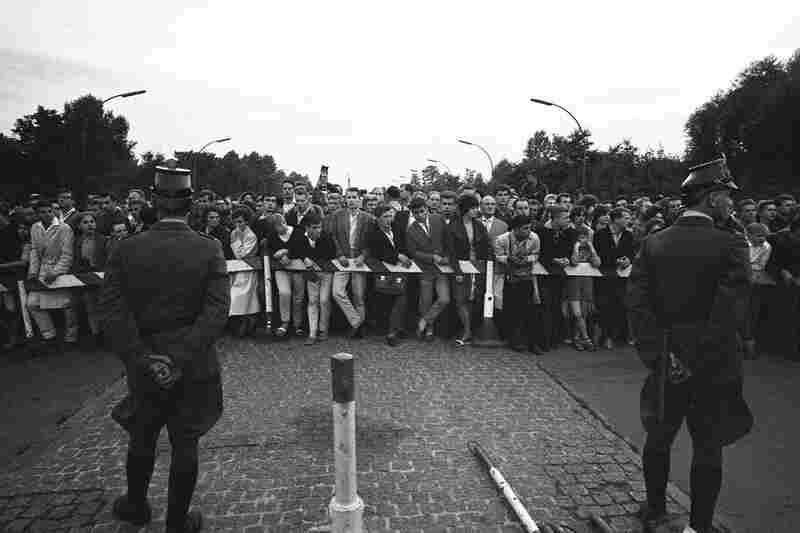 """West Berliners protest an East German border blockade two days after construction of the wall began. President Kennedy approached the situation with a passive attitude, saying, """"A wall is not nice, but it's a helluva lot better than a war."""""""