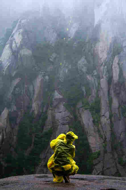 """A photographer stops to take a picture of the vertical staircase that is etched into the side of this mountain leading toward the peak ... at Huang Shan (Yellow Mountain) in China."""