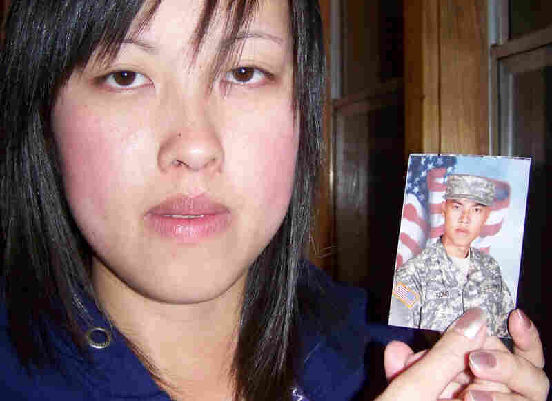 Kham XiongMee Xiong of St. Paul, Minn., holds a photo of her older brother, Kham Xiong, 23. Originally from Laos, Kham came to the U.S. as a toddler. He leaves behind a wife and three children.