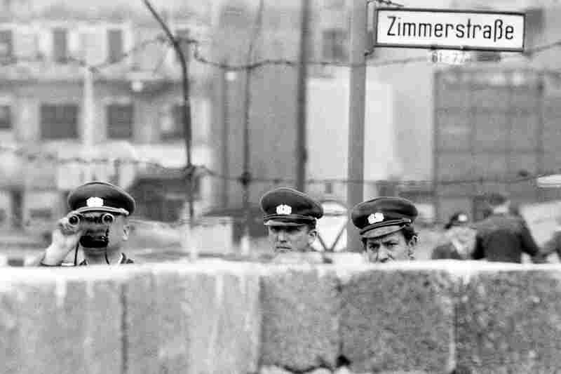 East German policemen peer into West Berlin over a temporary portion of the Berlin Wall. East Berliners were closely monitored by the notorious Stasi, the Ministry for State Security.