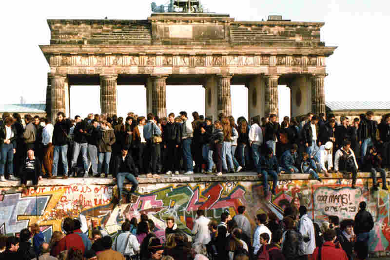 People walk freely atop the Berlin Wall in front of the Brandenburg Gate on Nov. 10, 1989, one day after the border between East and West Berlin was opened.