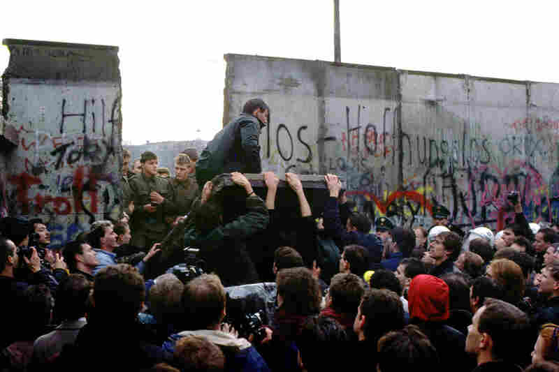 East and West Berliners tear down a portion of the Berlin Wall. The fall of the Berlin Wall was in many ways symbolic of the end of the Cold War.