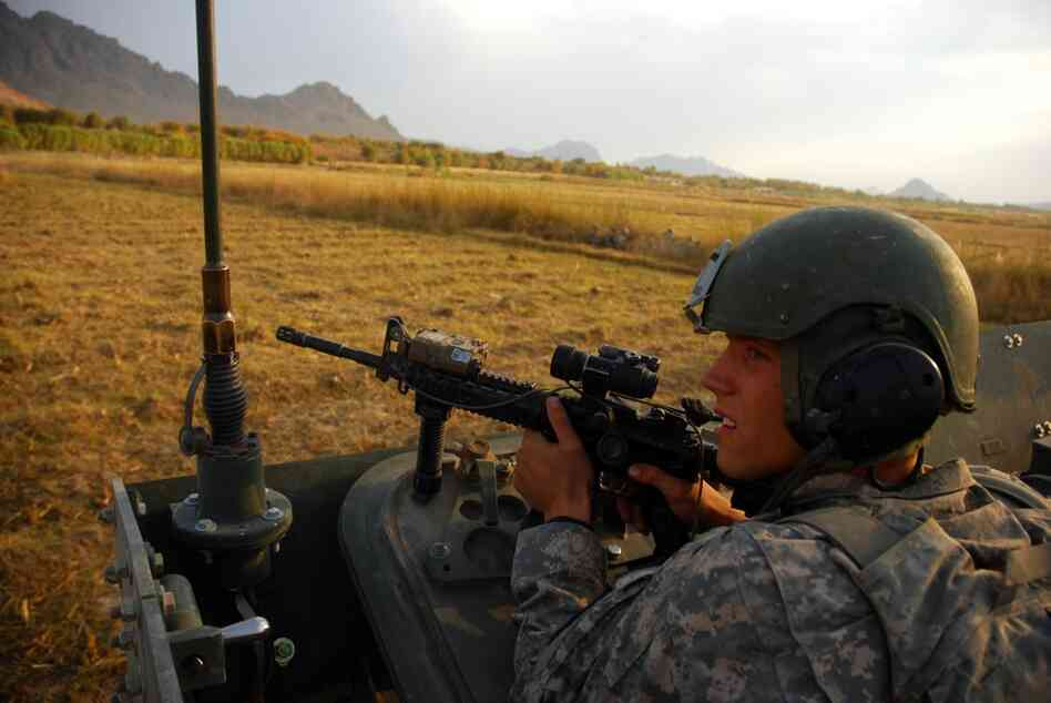 Spc. Riley Sheffield of Boise, Idaho, looks towards a tree line as insurgents fire on the convoy, just after the roadside bomb exploded. Soldiers from Charlie Company exchanged fire with insurgents for over an hour. Sheffield is on his first deployment.