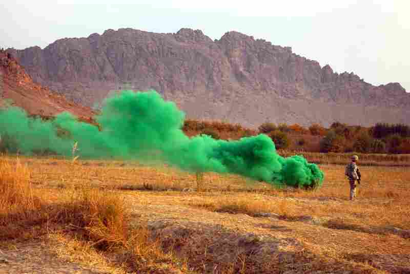 "A green smoke grenade marks the landing zone for a helicopter that will carry away the two wounded soliders.  The military seeks to evacuate casualties as quickly as possible – within what's known as the ""golden hour."""