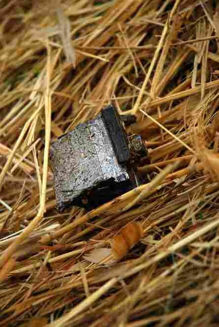 Parts of the broken and burning Stryker are scattered around the field. Some are small, like this piece of metal. But a 1,000-pound section of the front end was thrown 300 yards from the blast site.