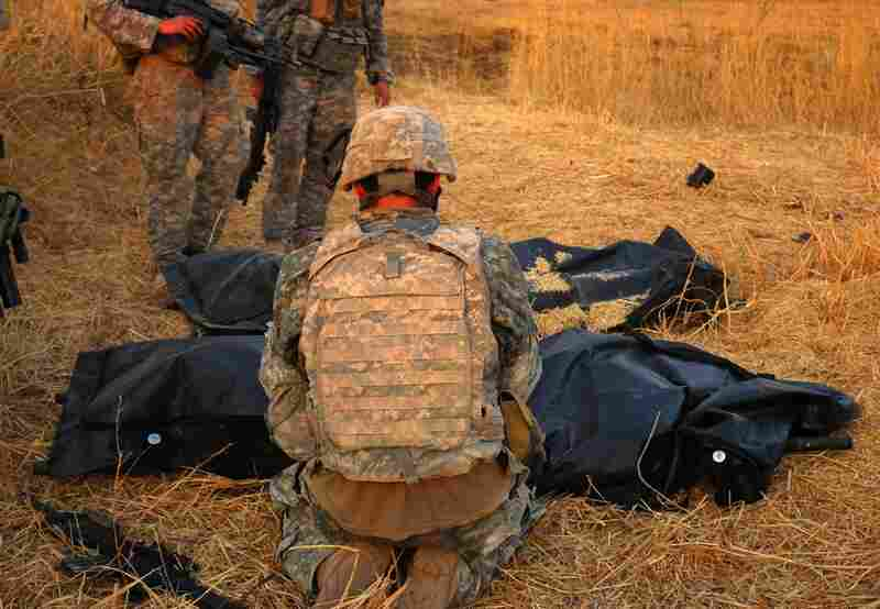 "A soldier kneels in front of the bodies of two of his fallen comrades. ""God bless you, brother,""  he said, touching one of the bags."