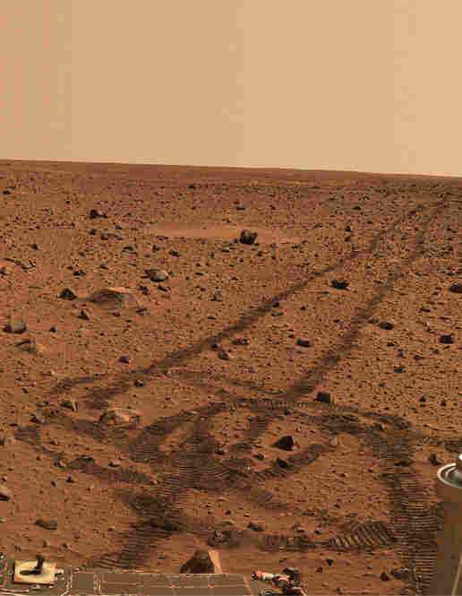 "While driving over the reddish rocks and soils of Mars, the rover's wheels dig below the thin dusty layer and reveal the darker, brownish soils below. The circular tracks are ""pirouettes"" that the rovers occasionally do to align their radio antennas for best possible communications."