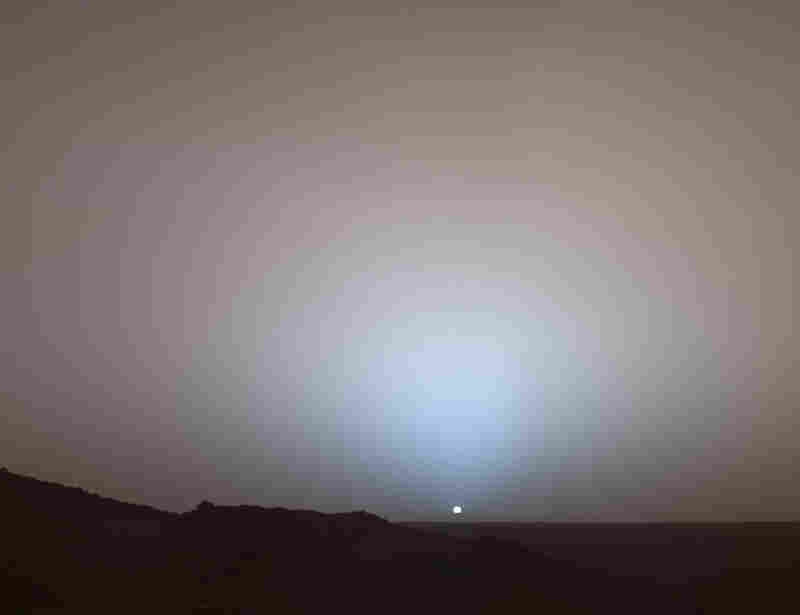Spirit rover watches a Martian sunset. The daytime sky is reddish-brown because it holds so much suspended dust. The same dust turns the sky bluish at sunset.