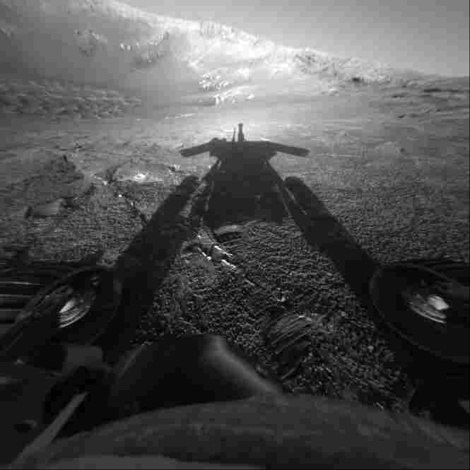 The setting sun casts a long rover shadow as Opportunity prepares to drive down into Endurance crater, a stadium-sized hole in the ground filled with sand dunes and layered rocks.