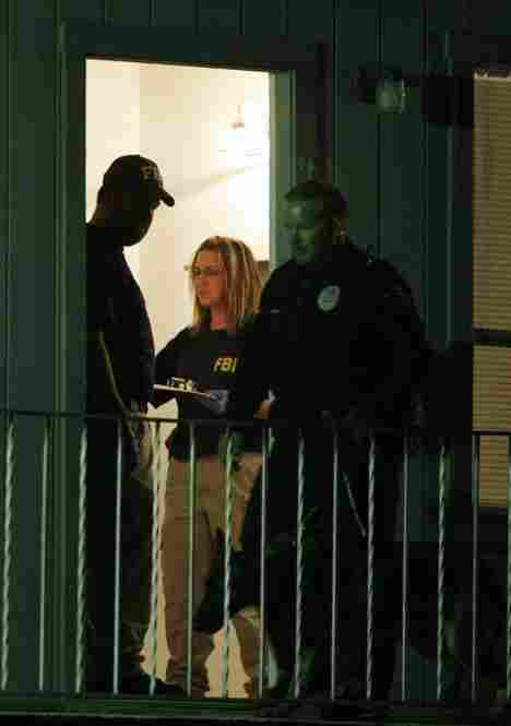 Federal agents search Hasan's apartment in Killeen early Friday. Hasan, an Army psychiatrist, was unconscious and on a ventilator Friday, contrary to early reports that he had been killed.