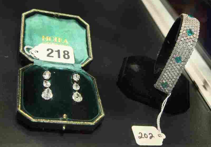 Silver pre-Victorian diamond earrings and a platinum Edwardian-era diamond and emerald bracelet.