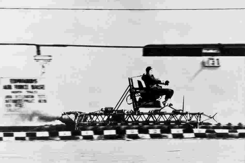Col. John Paul Stapp, an Air Force medical doctor, rides a rocket sled at Edwards Air Force Base.  Between the late 1940s and mid-1950s, Stapp was one of the Air Force's most frequent volunteers in human deceleration testing. In his last run aboard the Sonic Wind I in 1954, Stapp accelerated to 632 mph in 5 seconds and decelerated in 1.4 seconds, experiencing 46.2 times the normal force of grav...
