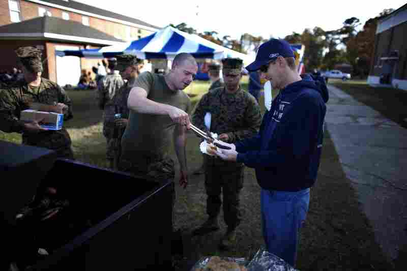 "George ""Mick"" Todd serves a hot dog to Tom Apsey as they wait for the return of Tom's son, Lance Cpl. Josh Apsey, on Nov. 17."