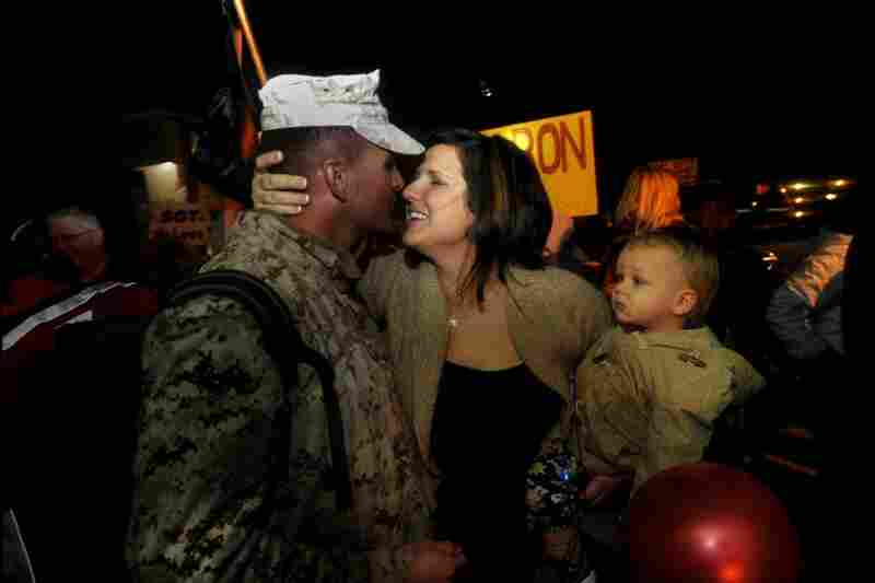 Lt. Brandon Currie of 1st Platoon, Golf Company finds the loving arms of his wife, Lynne, and 1-year-old son, Carson, as he steps off the bus on Nov. 14.
