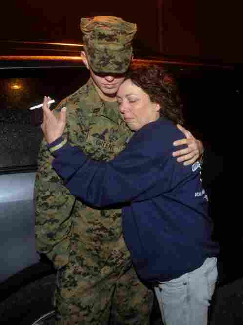 Delma Posey, the mother of Lance Cpl. Gregory Posey who died in action in July, hugs her son's friend, Navy medic Richie Greene, while waiting for the buses to arrive. Posey came to support the soldiers of Golf Company despite the fact that her son did not return with them.