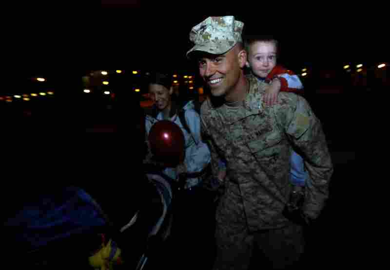 First Lt. Nick Bourgeois of 1st Platoon, Golf Company gives his 2-year-old son Schriever a piggyback ride while his wife, Miranda, pushes their 3-month-old David in a stroller after reuniting at Camp Lejeune on Nov. 14.