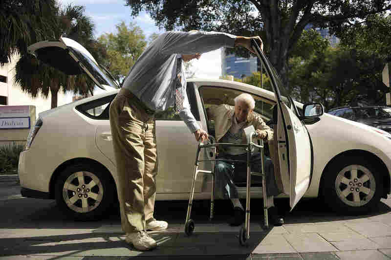 "Seymour assists Gruner as he gets out of the car at his doctor's office in Winter Park, Fla. ITN offers door ""through"" door service, which guarantees the driver will pick up passengers inside their homes and escort them into their destinations."