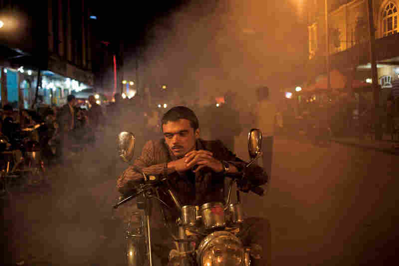 A motorcycle taxi driver waits for his next customer at a night market in Kashgar. Limited job opportunities tend to stall many Uighurs as the wealth disparity widens. According to a U.S. government report, the Xinjiang Production and Construction Corps recently reserved some 800 of its 840 civil service jobs for Han workers.
