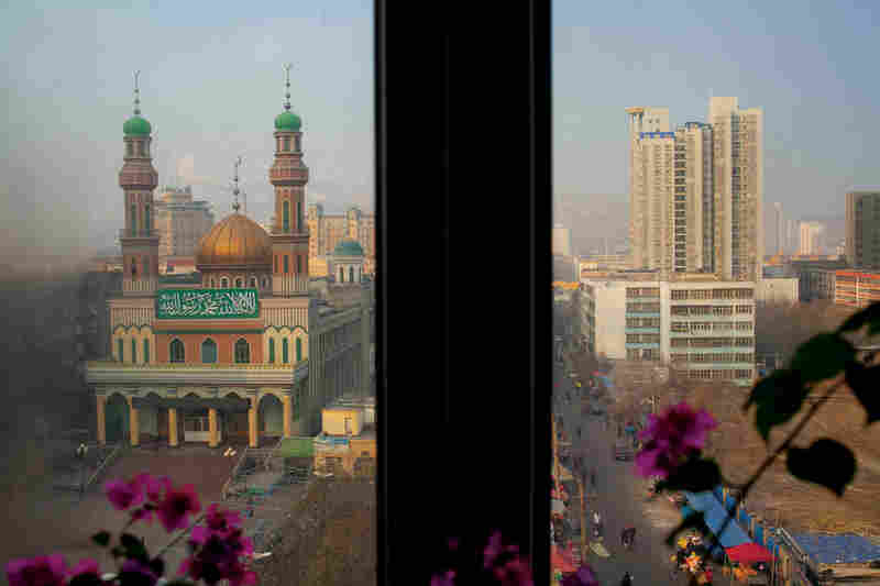 A window frame splits the view of Urumqi's Noghay Mosque from Chinese-style development.