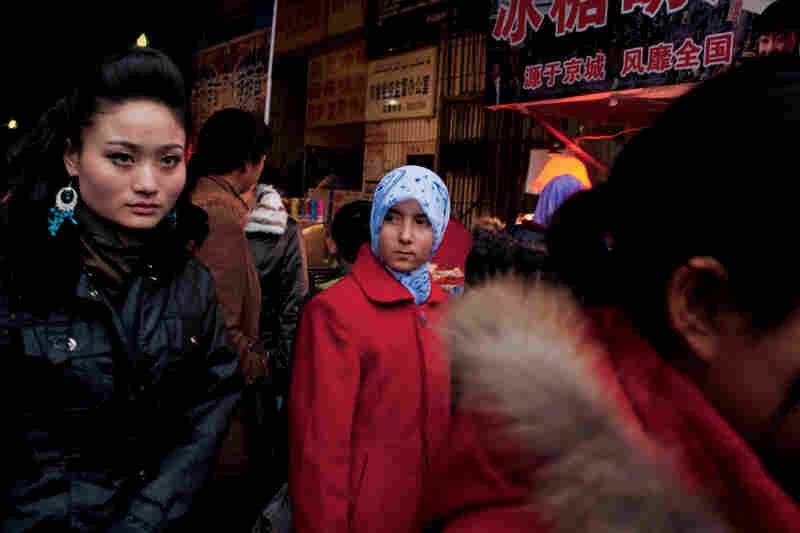 A Uighur woman (right) shops at a Chinese market in Karamay, an oil-industry city dominated by Han Chinese. Uighurs hold few top jobs, although they constitute nearly half of Xinjiang province's population.