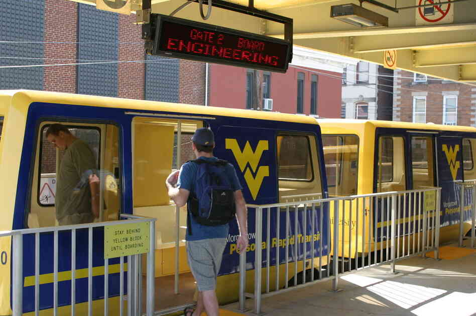 A student boards the West Virginia University pod car at one of the five platforms along the route. The system was constructed in 1975 and can transport about 4,000 people an hour.