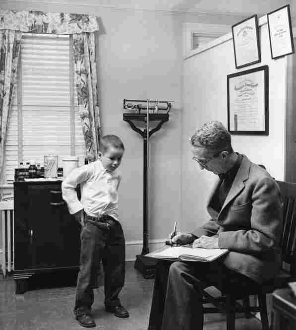 Kalischer reluctantly agreed to help his neighbors by shooting photos for Rockwell's illustrations. But he also worked as a documentarian, taking pictures of Rockwell and his models as they worked. Here, in 1958, Rockwell writes a check to child model Ed Locke after staging what would become the iconic illustration Before the Shot.