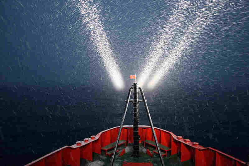 Spotlights illuminate the water during a surprise snow squall.