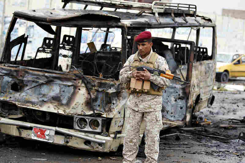An Iraqi soldier stands at the site of an explosion on Cairo Street where a suicide attacker had blown up his car near the Ministry of Labor.