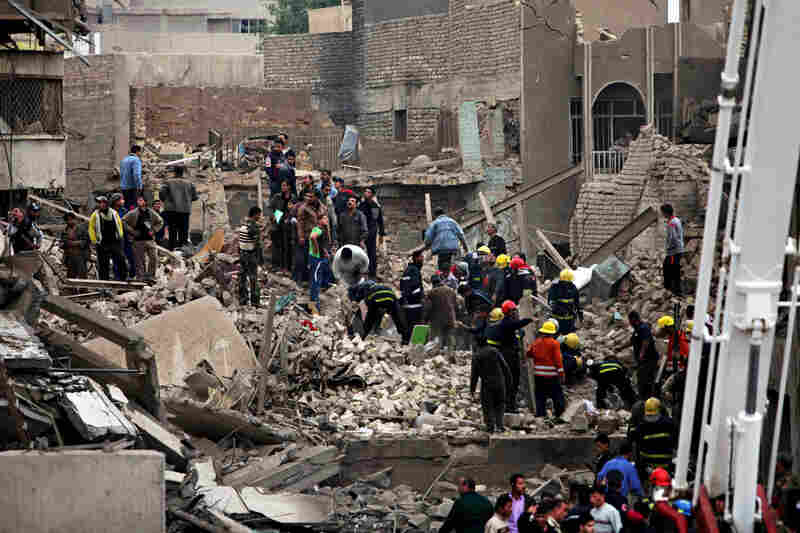 Iraqi security forces and rescuers search for survivors in the rubble of a bomb attack near the new site of the Finance Ministry. A series of five coordinated attacks Tuesday left at least 127 dead and wounded more than 500 in Baghdad.