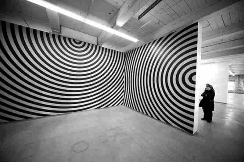 Wall Drawing #462: On four walls, one room, arcs 4 inches (10 cm) wide, from the midpoints of four sides, drawn with alternating bands of gray and black ink wash, January 1986.