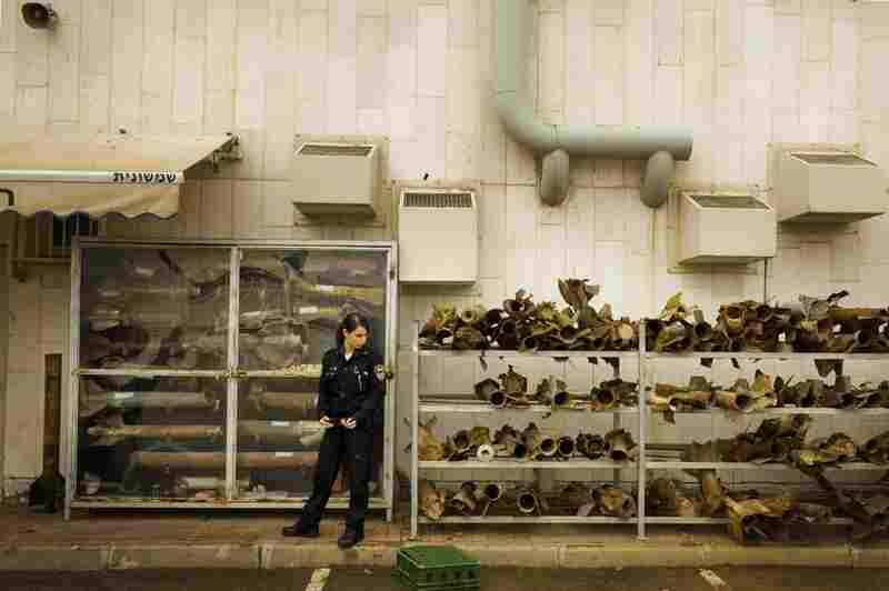 Police officer Tzlil Levi stands in front of the collected remains of rockets fired from Gaza on the city of Sderot.