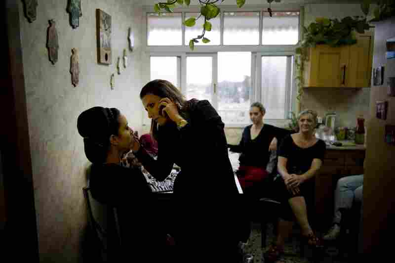 Revital Chai applies makeup to Moriya Sabag (left) while Moriya's mother, Alice Sabag, (far right) and sister Keren Sabag watch. The women were preparing for Alice's son's wedding, which was held in Jerusalem instead of Sderot for fear of rocket fire from Gaza.