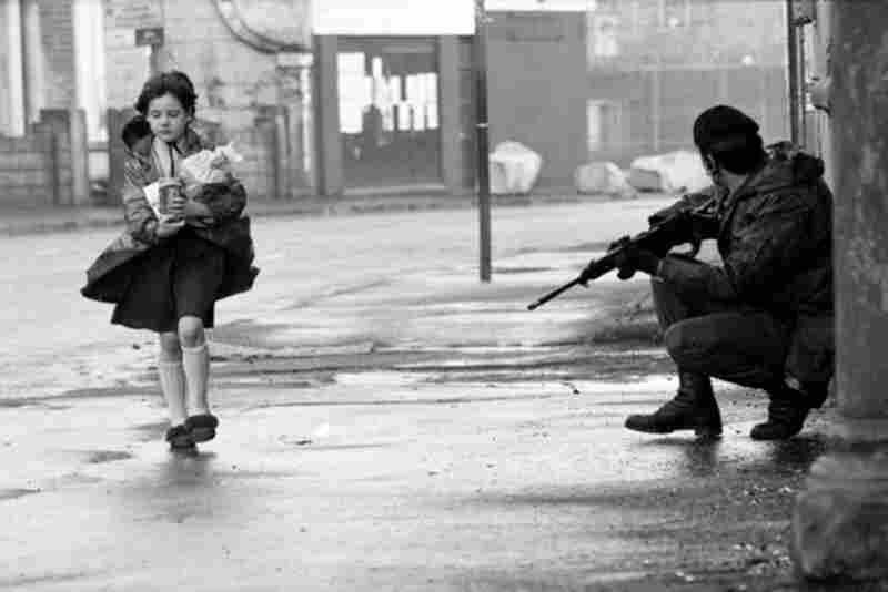 """""""When I got to know members of the Irish Republican Army, they told me that if you saw children you wouldn't see any trouble, bombing, or shooting; but if there were no children around: beware."""" Young Girl and British Soldier, Belfast,  Ireland, 1969"""