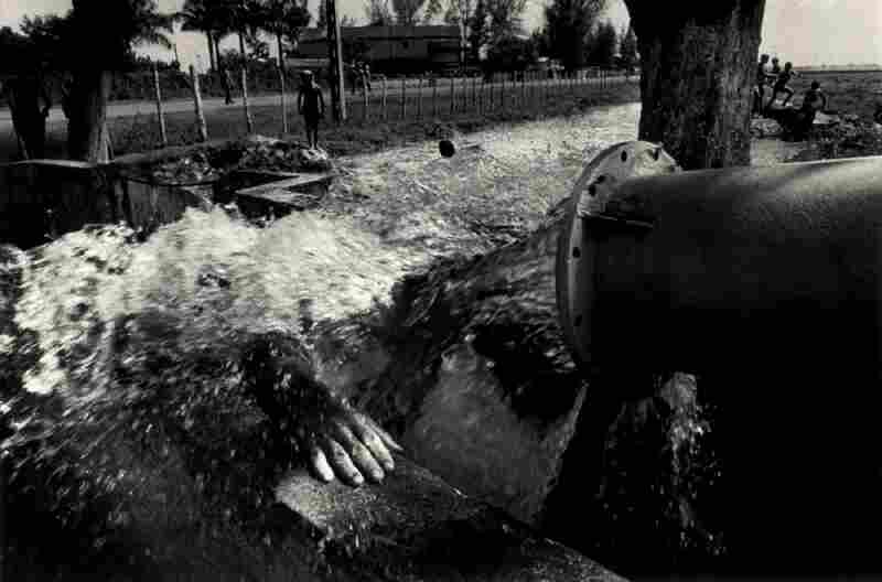 A man showers on a hot summer day, near Giron, 1996.