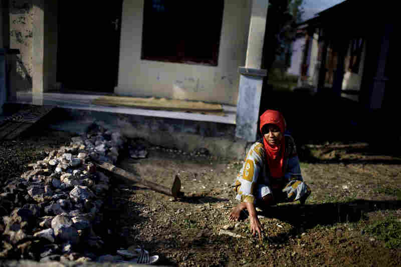 A woman sifts through dirt, pulling weeds in front of her new home, which was built by the Irish Red Cross. The tsunami killed a disproportionate number of women and children.