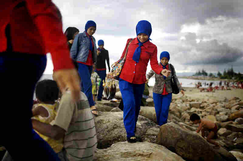 Acehnese women walk along a new jetty. Many families now head to the beaches on Sundays to relax.