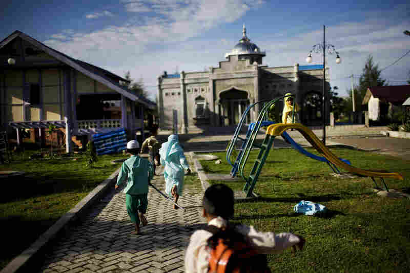 Children run to a newly built mosque in their neighborhood. The tsunami devastated the neighborhood, killing most of its residents.