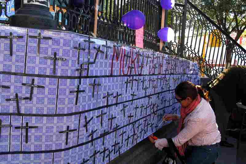 Resident Diana Martinez, 29, attaches the name of her brother, Rafael, to a banner honoring those killed in the recent violence.